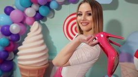 Εύθυμο κορίτσι που κρατά τα ρόδινα παπούτσια στα χέρια της απόθεμα βίντεο