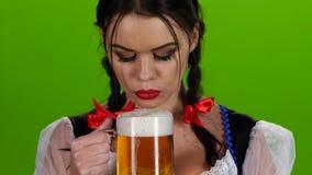 Εύθυμο κορίτσι που φυσά ένα ποτήρι της μπύρας και των χαμόγελων πράσινη οθόνη φιλμ μικρού μήκους