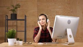 Εύθυμο κορίτσι στο γραφείο που ακούει τη μουσική στα ακουστικά φιλμ μικρού μήκους