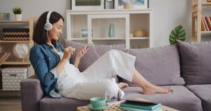 Εύθυμο κορίτσι χρησιμοποιώντας το smartphone και ακούοντας τη μουσική στα σύγχρονα ακουστικά φιλμ μικρού μήκους