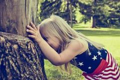 Εύθυμο κρύψιμο μικρών κοριτσιών πίσω από το δέντρο Στοκ Εικόνες