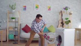 Εύθυμο μέσης ηλικίας άτομο που συμμετέχεται στα πράγματα και τους χορούς πλυσιμάτων οικιακών μικροδουλειών απόθεμα βίντεο