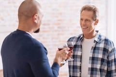 Εύθυμο μη παραδοσιακό κρασί κατανάλωσης ζευγών στο σπίτι Στοκ Εικόνες