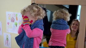 Εύθυμο μικρό κορίτσι και η μητέρα της που παίζουν κοντά στον καθρέφτη απόθεμα βίντεο