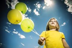 Εύθυμο μικρό κορίτσι με τα ζωηρόχρωμα μπαλόνια θερινό ηλιόλουστο swallowtail χλόης ημέρας πεταλούδων Γωνία από κάτω από Στοκ Εικόνα