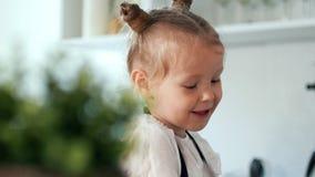 Εύθυμο μικρό κορίτσι με τη μητέρα της που έχει τη διασκέδαση στην κουζίνα απόθεμα βίντεο