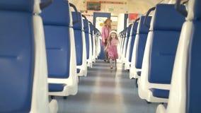 Εύθυμο μικρό κορίτσι με τους περιπάτους mom της στο κενό αυτοκίνητο τραίνων φιλμ μικρού μήκους