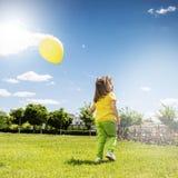 Εύθυμο μικρό κορίτσι με το μπαλόνι θερινό ηλιόλουστο swallowtail χλόης ημέρας πεταλούδων Στοκ φωτογραφία με δικαίωμα ελεύθερης χρήσης