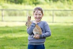 Εύθυμο μικρό κορίτσι που κρατά ένα πραγματικό κουνέλι Στοκ Εικόνα