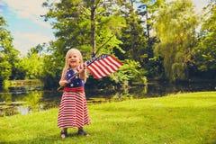 Εύθυμο μικρό κορίτσι που κυματίζει την ΑΜΕΡΙΚΑΝΙΚΗ σημαία στο πάρκο Στοκ Φωτογραφίες