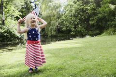 Εύθυμο μικρό κορίτσι που περπατά με τη αμερικανική σημαία Στοκ Εικόνες