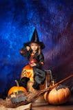 Εύθυμο μικρό κορίτσι σε μια συνεδρίαση κοστουμιών μαγισσών σε ένα ξύλινο barr Στοκ εικόνα με δικαίωμα ελεύθερης χρήσης