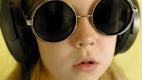 Εύθυμο μικρό κορίτσι στα ακουστικά σε ένα κίτρινο υπόβαθρο r απόθεμα βίντεο