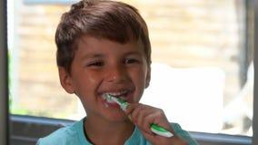 Εύθυμο μικρό παιδί που βουρτσίζει τα δόντια του απόθεμα βίντεο