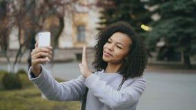 Εύθυμο μικτό κορίτσι σπουδαστών φυλών που μιλά στην τηλεοπτική κλήση με το smartphone κοντά στο univercity απόθεμα βίντεο