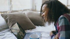 Εύθυμο μικτό κορίτσι φυλών που έχει την τηλεοπτική συνομιλία με τους φίλους που χρησιμοποιούν τη κάμερα lap-top στο κρεβάτι φιλμ μικρού μήκους