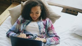 Εύθυμο μικτό κορίτσι φυλών που έχει την τηλεοπτική συνομιλία με τους φίλους που χρησιμοποιούν τη κάμερα lap-top στο κρεβάτι απόθεμα βίντεο