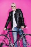 Εύθυμο μοντέρνο ανώτερο άτομο που φορά το σακάκι δέρματος και sunglesses που στέκεται με το ποδήλατο Στοκ Φωτογραφίες