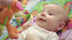 Εύθυμο μωρό που χαμογελά στο χαλί ανάπτυξης ευτυχές πορτρέτο μωρών φιλμ μικρού μήκους