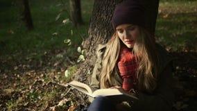 Εύθυμο νέο καυκάσιο κορίτσι που διαβάζει ένα βιβλίο στο πάρκο το φθινόπωρο φιλμ μικρού μήκους