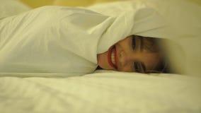 Εύθυμο νέο κορίτσι με τα κόκκινα χείλια σε ένα άσπρο κάλυμμα στο κρεβάτι φιλμ μικρού μήκους