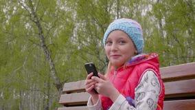 Εύθυμο νέο κορίτσι που μιλά και που χρησιμοποιεί το τηλέφωνο στον πάγκο στο πάρκο φιλμ μικρού μήκους