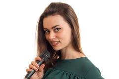 Εύθυμο νέο κορίτσι που χαμογελά στη κάμερα με το μικρόφωνο στα χέρια Στοκ Φωτογραφία