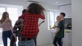 Εύθυμο νέο κόμμα φίλων στο σπίτι που έχει τη διασκέδαση και που χορεύει ενώ το κορίτσι παίζει την κιθάρα στο διαμέρισμα απόθεμα βίντεο
