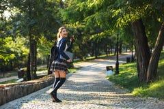 Εύθυμο νέο σχολικό κορίτσι που περπατά υπαίθρια στοκ εικόνα με δικαίωμα ελεύθερης χρήσης