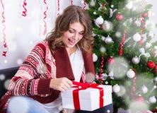 Εύθυμο νέο δώρο Χριστουγέννων ανοίγματος γυναικών κοντά στο χριστουγεννιάτικο δέντρο Στοκ Εικόνα