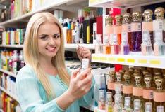 Εύθυμο ξανθό άρωμα αγοράς κοριτσιών στο τμήμα αρώματος Στοκ Φωτογραφίες