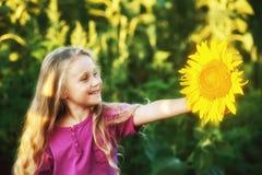 Εύθυμο ξανθό κορίτσι που κρατά ένα λουλούδι ηλίανθων στα χέρια της στοκ φωτογραφία με δικαίωμα ελεύθερης χρήσης