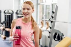 Εύθυμο δοκιμάζοντας ποτό γυναικών κατά τη διάρκεια του workout Στοκ Φωτογραφία