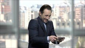 Εύθυμο παίζοντας παιχνίδι επιχειρηματιών στο τηλέφωνο στην αρχή απόθεμα βίντεο