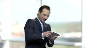 Εύθυμο παίζοντας παιχνίδι επιχειρηματιών στο smartphone του φιλμ μικρού μήκους