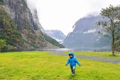 Εύθυμο παιδάκι που τρέχει και που παίζει στο του χωριού λιμάνι Gudvangen, ένας δημοφιλής τόπος προορισμού τουριστών τοποθετημένος στοκ φωτογραφίες