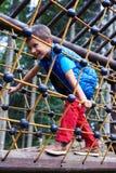 Εύθυμο παιχνίδι αγοριών στην αναρρίχηση καθαρή στην παιδική χαρά Στοκ Εικόνες