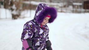 Εύθυμο παιχνίδι παιδιών στο πρώτο χιόνι το χειμώνα Χρονών αγοράκι στο θερμό κοστούμι χιονιού που περπατά και που έχει τη διασκέδα φιλμ μικρού μήκους