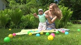 Εύθυμο παιχνίδι μητέρων με το μωρό στο λιβάδι 4K απόθεμα βίντεο