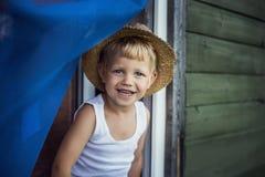Εύθυμο παιδί με το καπέλο αχύρου που κλίνει έξω ένα παράθυρο Στοκ φωτογραφία με δικαίωμα ελεύθερης χρήσης