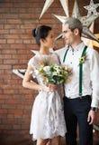 Εύθυμο παντρεμένο ζευγάρι κοντά στο τουβλότοιχο Στοκ φωτογραφίες με δικαίωμα ελεύθερης χρήσης