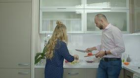 Εύθυμο περιστασιακό ζεύγος που προετοιμάζει τα τρόφιμα στην κουζίνα απόθεμα βίντεο