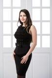 Εύθυμο πρότυπο μαύρο φόρεμα μόδας που θέτει και που χαμογελά στις εγχώριες εσωτερικές πόρτες σοφιτών στούντιο πίσω στοκ εικόνα με δικαίωμα ελεύθερης χρήσης