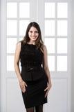 Εύθυμο πρότυπο μαύρο φόρεμα μόδας που θέτει και που χαμογελά στις εγχώριες εσωτερικές πόρτες σοφιτών στούντιο πίσω στοκ εικόνες