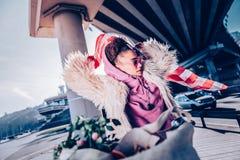 Εύθυμο σγουρός-μαλλιαρό κορίτσι που φορά το παλτό γουνών eco στοκ εικόνες