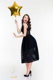 Εύθυμο συγκινημένο θηλυκό με το αναδρομικό διαμορφωμένο αστέρι μπαλόνι εκμετάλλευσης hairstyle Στοκ Φωτογραφίες