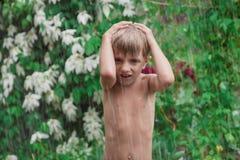 Εύθυμο, συγκινημένο μωρό που έχει τη διασκέδαση, που τρέχει υγρή κατώτερη τη βροχή Στοκ Εικόνες