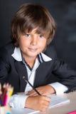 Εύθυμο σχολικό αγόρι που γράφει στο σημειωματάριο Στοκ εικόνες με δικαίωμα ελεύθερης χρήσης
