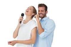 Εύθυμο τραγούδι ζευγών στα μικρόφωνα Στοκ Φωτογραφία