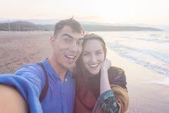 Εύθυμο χαμογελώντας ζεύγος selfie στην παραλία στις ακτίνες του ήλιου ηλιοβασιλέματος Στοκ εικόνες με δικαίωμα ελεύθερης χρήσης